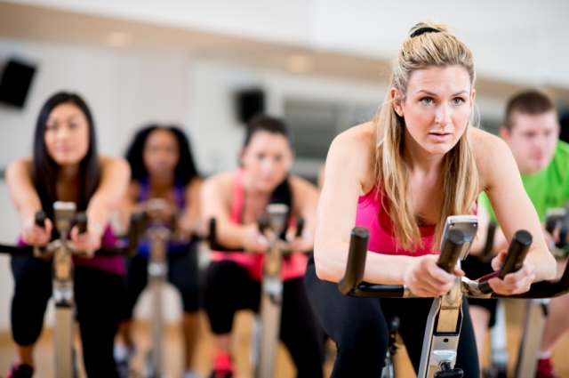 A group of young adults concentrating hard while working out in a spinning class at the gym